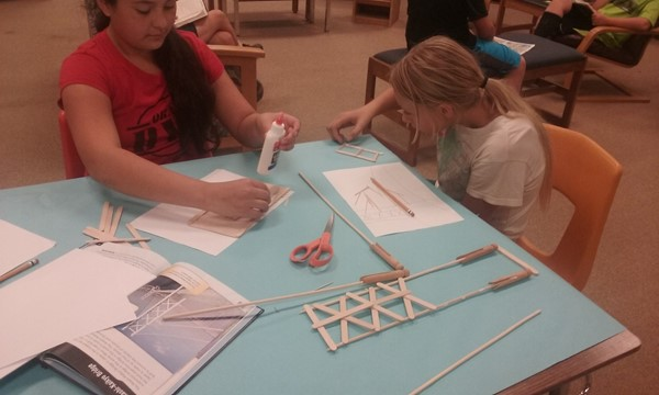 Students in grades 3-6 construct bridges.
